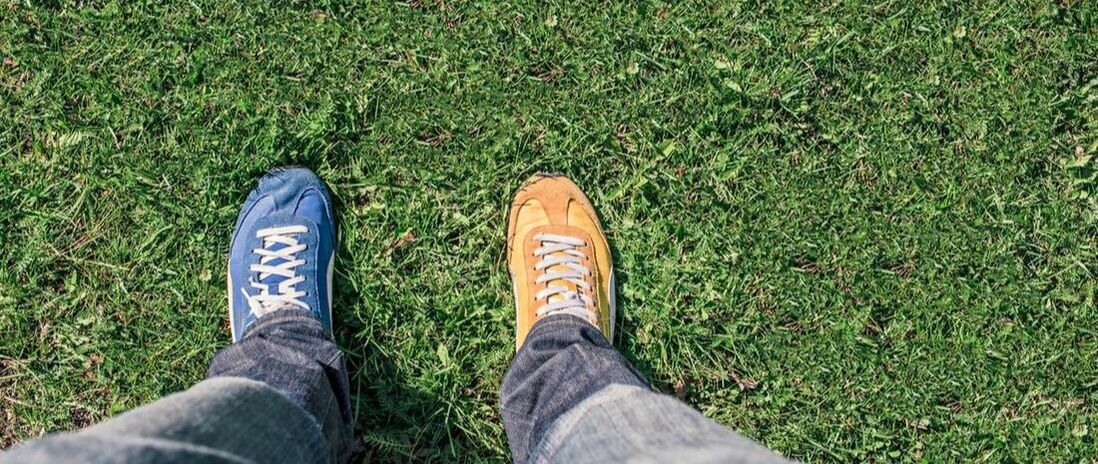 Person wearing one blue sneaker and one gold sneaker standing on green grass